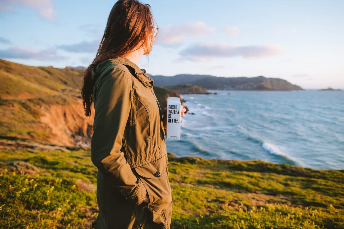 woman in brown jacket standing on green grass field near body of water during daytime